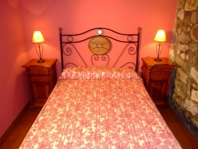 Cama de matrimonio y pared rosa