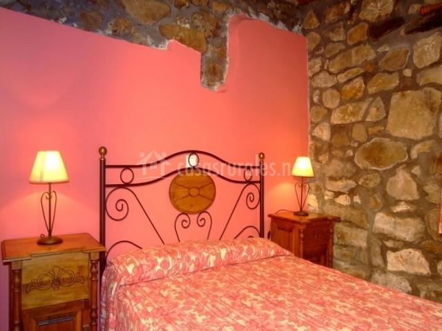 Dormitorio con pared rosa y de piedras con cama doble