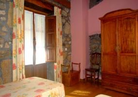 Dormitorio abuhardillado con paredes de piedra y rosas