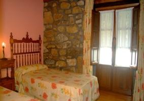 Dormitorio con dos camas individuales y salida a terraza