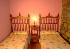 Dormitorio con dos camas y paredes rosas