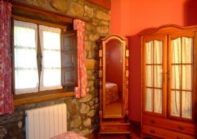Dormitorio de matrimonio con armario y espejo