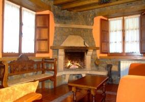 Sala de estar con sillones en torno a chimenea