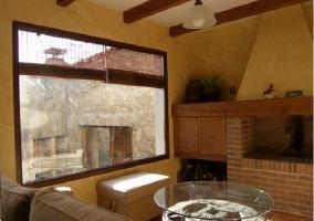 Salón con ventanal y chimenea de leña