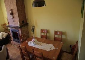 Amplio salón comedor amueblado en torno a chimenea de piedra