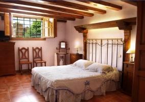 Dormitorio con techo de vigas de madera