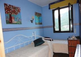 Dormitorio azul con dos camas y vistas a las montañas