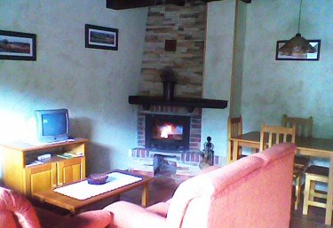 Living room with orange armchairs in front of the television and with fireplace