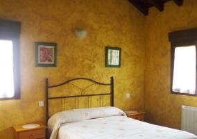 Dormitorio de matrimonio con las paredes de color amarillo
