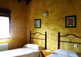 Dormitorio doble con dos camas y paredes amarillas