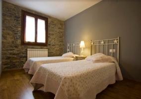 Dormitorio doble con suelos de madera y ventana