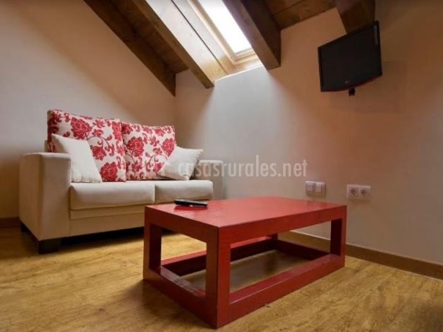 Sala de estar con detalles en rojo y suelo de madera