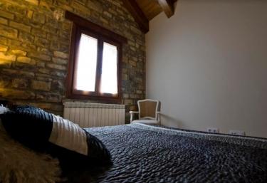 Dormitorio de matrimonio con sus paredes en piedra