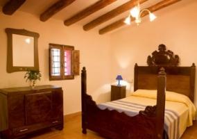 Dormitorio de matrimonio con cabecero tallado y vigas en madera