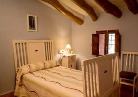 Dormitorio individual con vigas de madera en el techo
