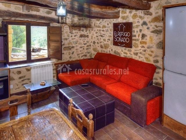 Salón con sofá chaise long y mesas en torno a la cocina