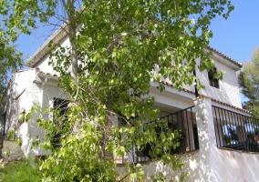 fachada blanca vista desde la zona de jardín con árboles