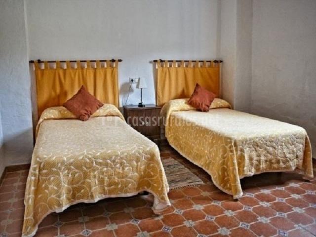 dormitorio con camas individuales de cabeceros de tela