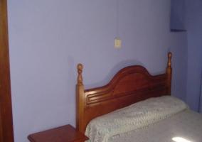 Dormitorio de matrimonio azul con cabecero de madera