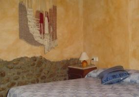 Dormitorio de matrimonio con pared de piedra