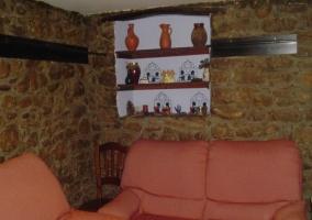 Sala de estar con sofás y pared de piedra