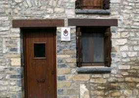Acceso a la casa en piedra y su puerta en madera