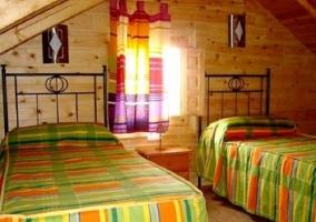 Dormitorio con camas individuales de colores y techo abuhardillado
