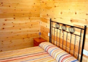 Dormitorio de matrimonio con paredes de madera