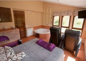 Dormitorio con jacuzzi sillones y televisor