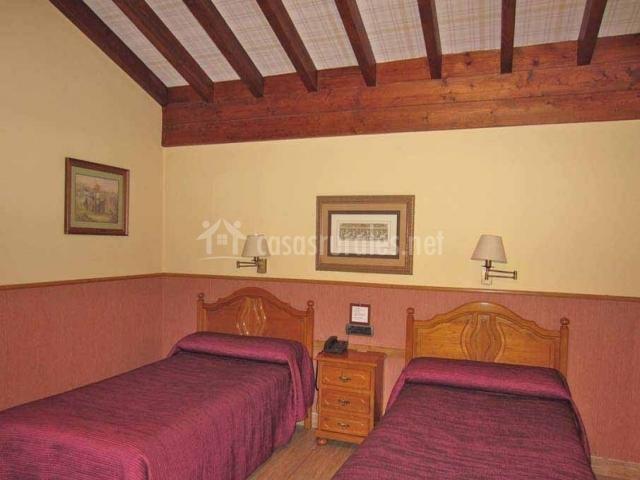 Dormitorio con techo con vigas de madera