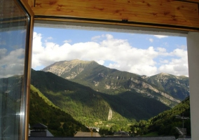 Fachada blanca de la casa rural con tejado de pizarra