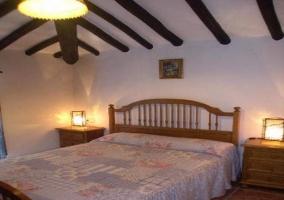 Dormitorio con techo atravesado por vigas de madera