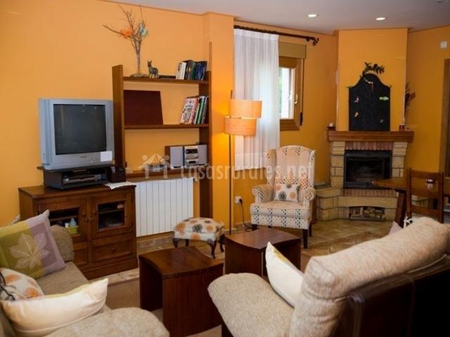 Detalle del salón con televisor y chimenea
