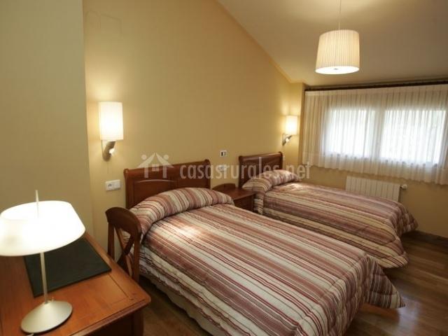 Dormitorio doble con techo abohardillado y escritorio