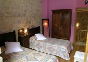 Dormitorio doble con muros de piedra