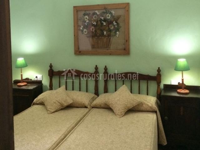 Dormitorio verde con dos camas juntas