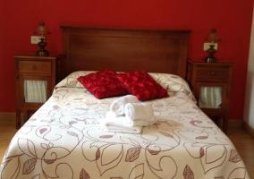 Dormitorio con cama doble y pared roja