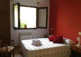 Dormitorio con pared roja y cama de matrimonio