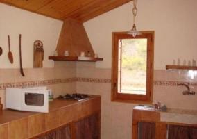 Sala de estar y comedor con una chimenea encendida y techos de madera