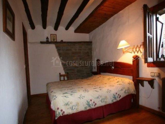 Dormitorio de matrimonio con cama amplia y ventanas