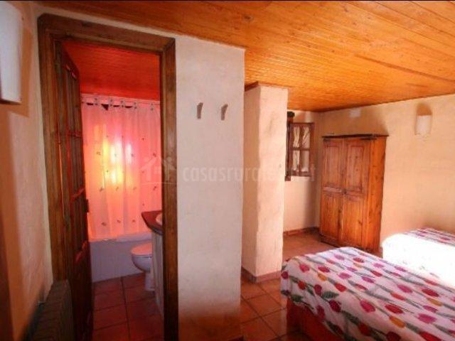 Dormitorio doble con aseo integrado y mobiliario funcional