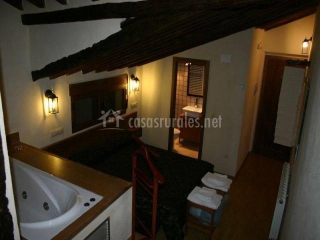 Dormitorio con aseo y bañera de hidromasaje