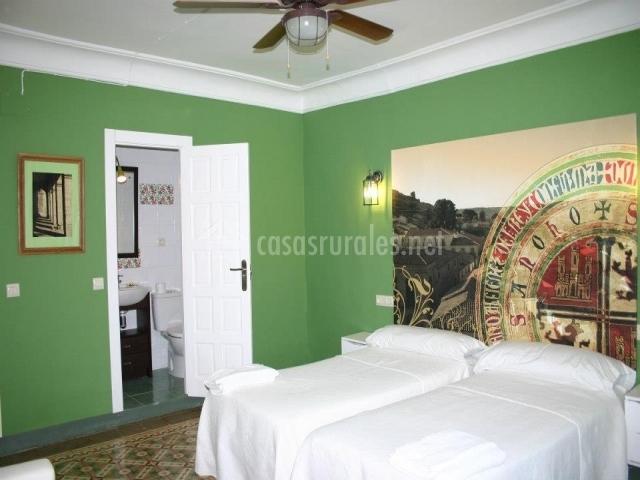 Dormitorio con paredes verdes y dos camas