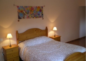 Dormitorio de matrimonio con cabecero de madera y cuadro colorido