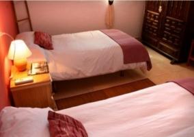 Dormitorio doble con detalles en tonos rojizos