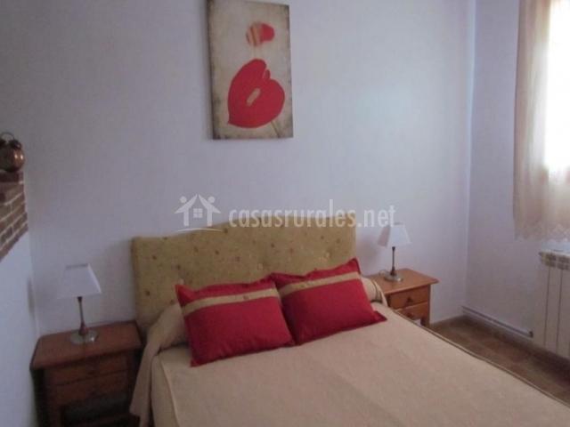 Dormitorio con cama de matrimonio y cuadro sobre el cabecero