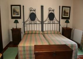 Dormitorio doble con camas juntas y cabeceros forjados