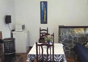 Sala de estar y cocina con microondas sobre la nevera