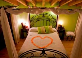 Dormitorio con cama con corazón de pétalos