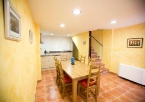 Mesa de comedor con la cocina al fondo